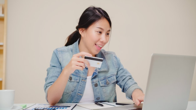 Beautiful asian woman using laptop buying online shopping by credit card while wear casual sitting on desk in living room at home.