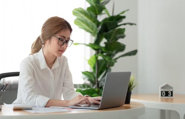 홈 오피스에서 노트북 컴퓨터를 사용하는 아름다운 아시아 여성.