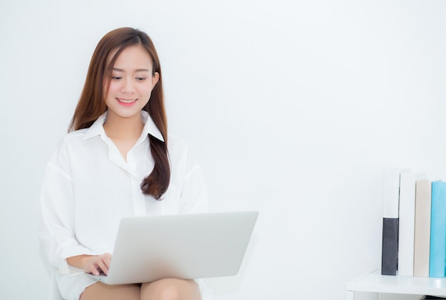 Beautiful asian woman using laptop for leisure on sofa.