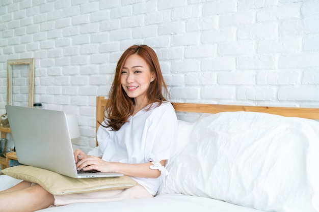 Beautiful asian woman using laptop n bed after wake up for checking email and social media, asian family and technology concept