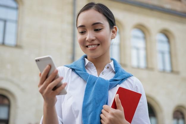 Красивая азиатская женщина с помощью мобильного телефона, общения, глядя на цифровой экран