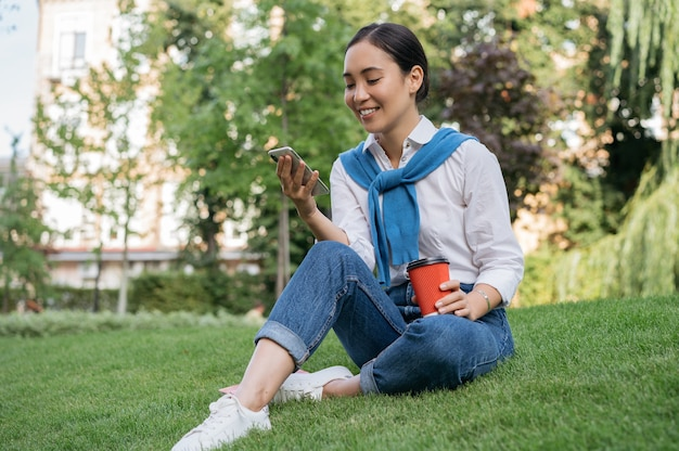 Beautiful asian woman using mobile phone, communication, watching movie, relaxing in green park, sitting on grass
