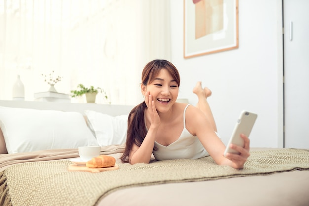 Beautiful asian woman using mobile phone to selfie while lying on bed
