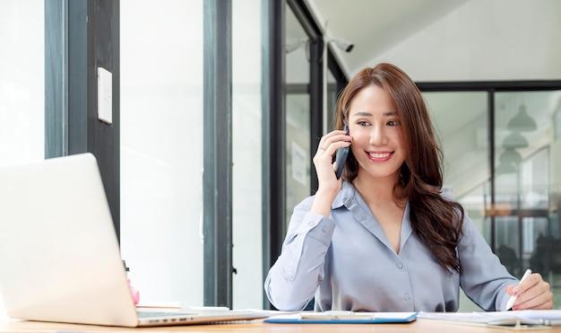 Красивая азиатская женщина с помощью мобильного телефона во время работы с портативным компьютером и оформлением документов в офисе.