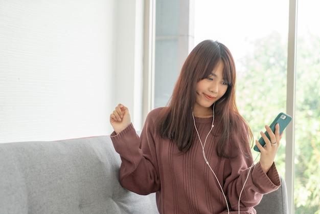 Красивая азиатская женщина с помощью смартфона на сером диване в гостиной