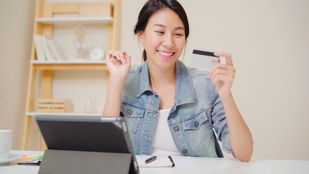 Beautiful asian woman using tablet buying online shopping by credit card while wear casual sitting on desk in living room at home.