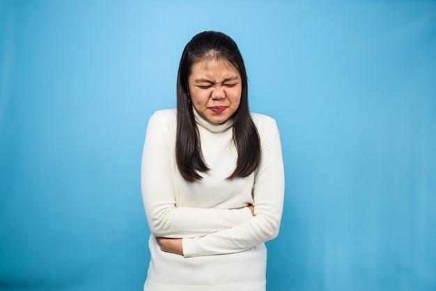 Красивая азиатская женщина, использующая белую футболку с концепцией жеста боли в животе синего изолированного фона