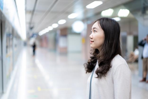 地下鉄(地下)プラットフォームで電車を待っている美しいアジアの女性