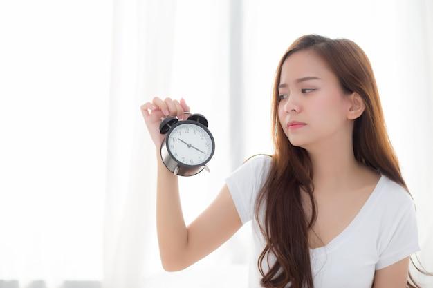 Beautiful asian woman wake up in morning annoyed alarm clock