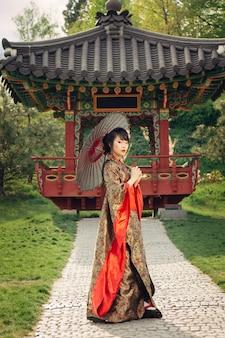Красивая азиатская женщина гуляя в сад