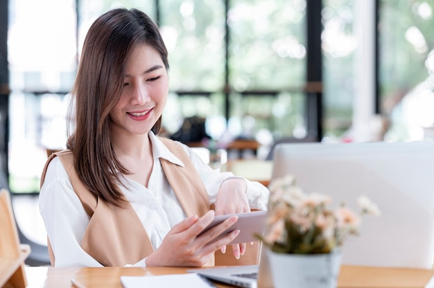 Красивая азиатская женщина смотрит видео на смартфоне, сидя за своим офисным столом.