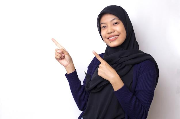 美しいアジアの女性は空のスペースにハンドポイントでヒジャーブを着用します。