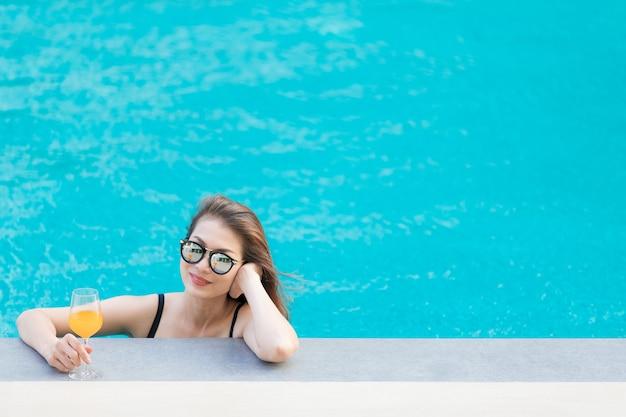 Красивая азиатская женщина носит бикини и солнцезащитные очки, стоя в бассейне с голубой водой с расслабляющей манерой, глядя в камеру со стаканом апельсинового сока.