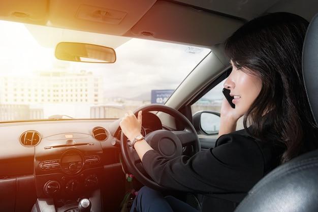 美しいアジアの女性は、日光の表面で夕方に車で携帯電話で話している黒いスーツの作業服を着ています