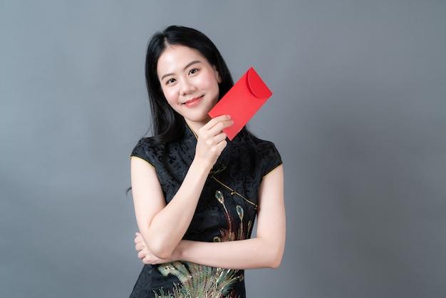 美しいアジアの女性は灰色の表面に赤い封筒で中国の伝統的なドレスを着ます