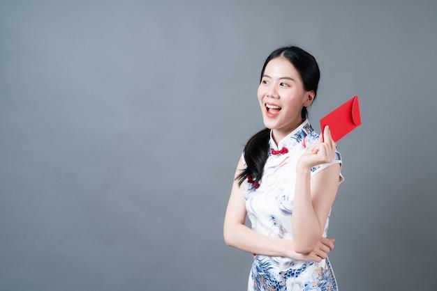 美しいアジアの女性は灰色の背景に赤い封筒または赤いパケットで中国の伝統的なドレスを着