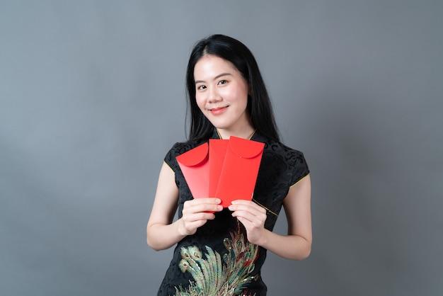 美しいアジアの女性は灰色の背景に赤い封筒または赤いパケットで中国の伝統的な衣装を着ています