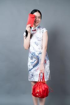 Красивая азиатская женщина носит китайское традиционное платье с красным конвертом или красным пакетом на сером фоне