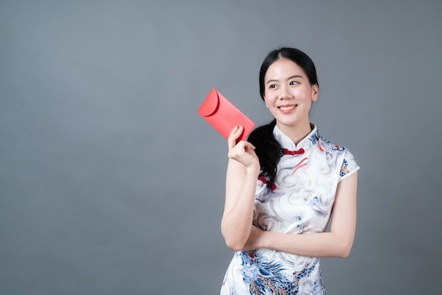 Красивая азиатская женщина носит китайское традиционное платье с красным конвертом или красным пакетом на серой стене