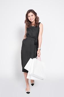 흰색 위에 쇼핑백이 서 있는 검은 드레스를 입은 아름다운 아시아 여성.