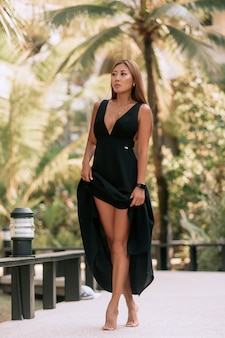 Beautiful asian woman wearing in black evening dress and watch, walking and cheerful smiling in the city. blurred palm trees .
