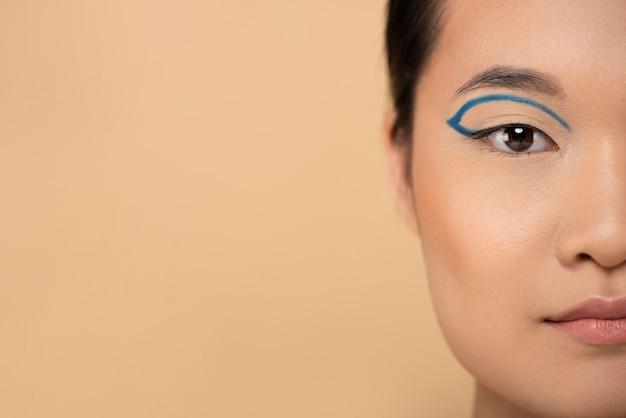 青いアイライナーを身に着けている美しいアジアの女性