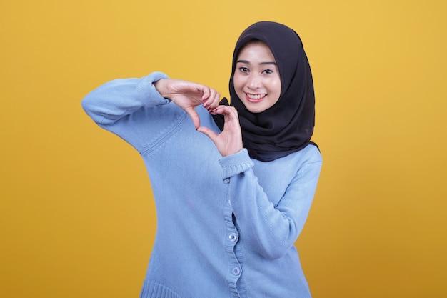 아름 다운 아시아 여자 캐주얼 옷을 입고 웃 고 보여주는 사랑 제스처를 제공