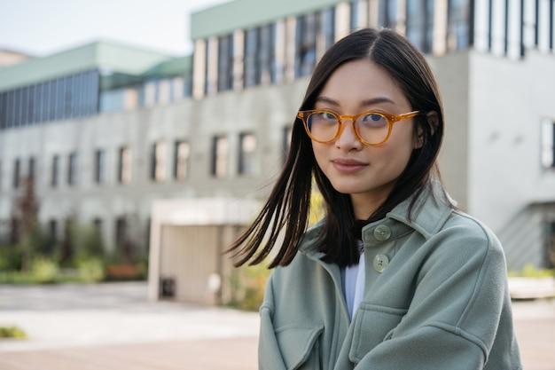カジュアルな服と屋外に立っているスタイリッシュな眼鏡を身に着けている美しいアジアの女性