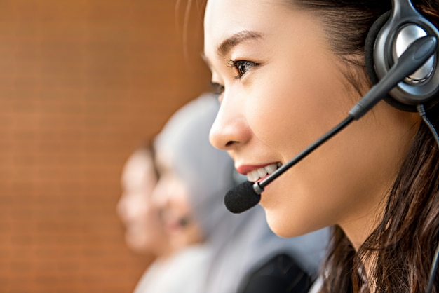 Beautiful asian woman wearing microphone headset working in call center