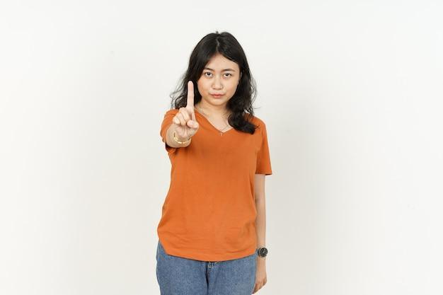白い背景で隔離の1本の指を示すオレンジ色のtシャツを着て美しいアジアの女性