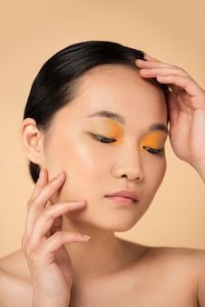 オレンジ色のアイシャドウを身に着けている美しいアジアの女性