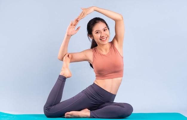 Красивая азиатская женщина в спортивной одежде и занимается йогой, фитнесом и тренажерным залом
