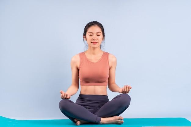 운동복을 입고 요가, 피트니스, 체육관 개념을 하는 아름다운 아시아 여성