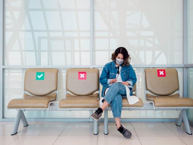 スマートフォンを使用して手術用フェイスマスクとジーンズのジャケットを着て、社会的な距離のサインと待機椅子に座っている美しいアジアの女性
