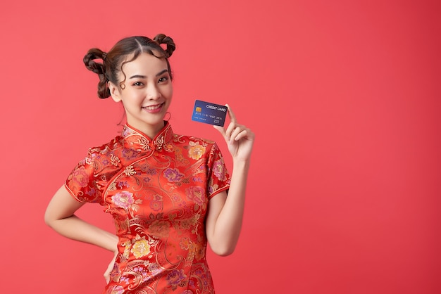 中国の旧正月のショッピングコンセプトのクレジットカードを示す伝統的なチャイナドレスのチャイナドレスを着ている美しいアジアの女性、