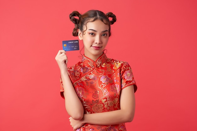 중국 새 해 쇼핑 개념에 대 한 빨간 벽에 신용 카드를 보여주는 전통적인 치파오 qipao 드레스를 입고 아름 다운 아시아 여자,