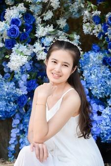 青い色の花の前に座っている白いドレスを着ている美しいアジアの女性。