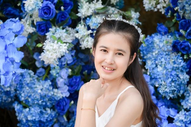 파란색 꽃 앞에 앉아 흰 드레스를 입고 아름 다운 아시아 여자.