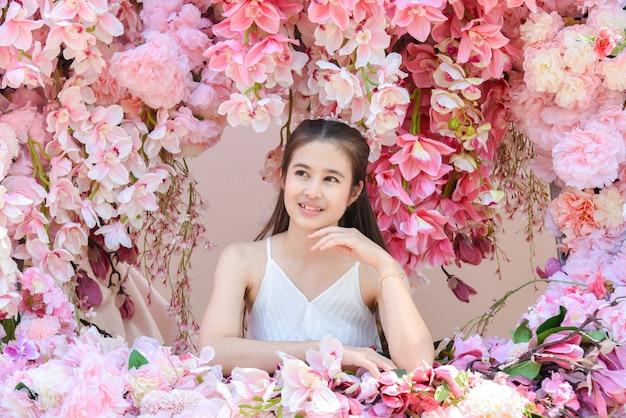 아름 다운 핑크 꽃과 함께 앉아 흰 드레스를 입고 아름 다운 아시아 여자.