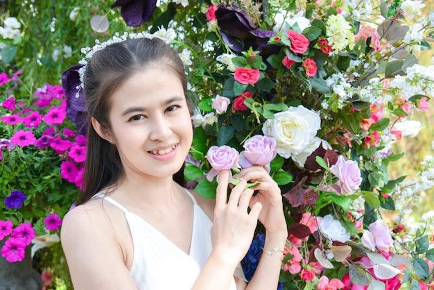 花畑に立っている白いドレスを着て美しいアジアの女性。フラワーパークで笑顔の花嫁。
