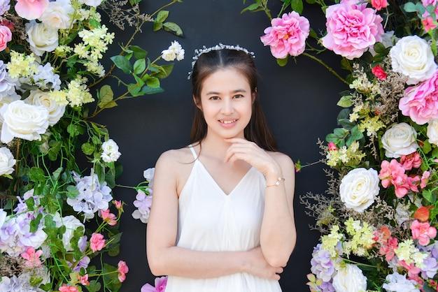 꽃과 검은 색 배경 앞에 서있는 흰색 드레스를 입고 아름 다운 아시아 여자.