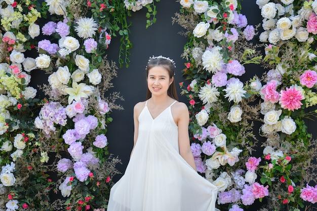 花と黒い色の背景の前に立っている白いドレスを着て美しいアジアの女性。