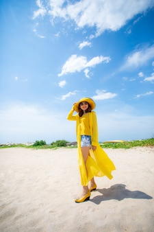 Beautiful asian woman wearing yellow clothes standing on sea beach against midday sun light