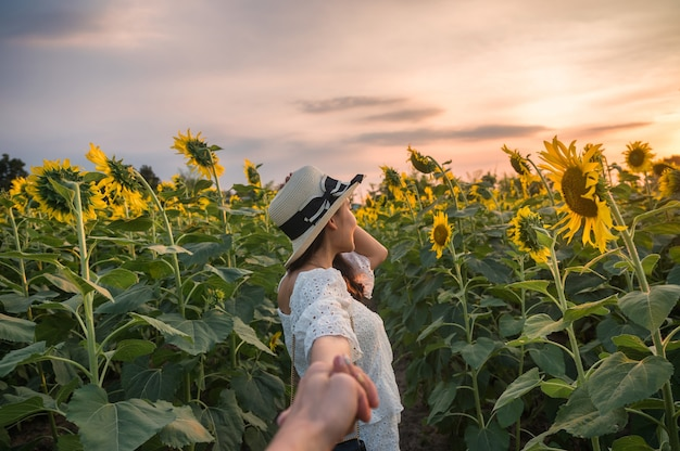 Beautiful asian woman in white dress holding hands a couple in sunflower field at evening