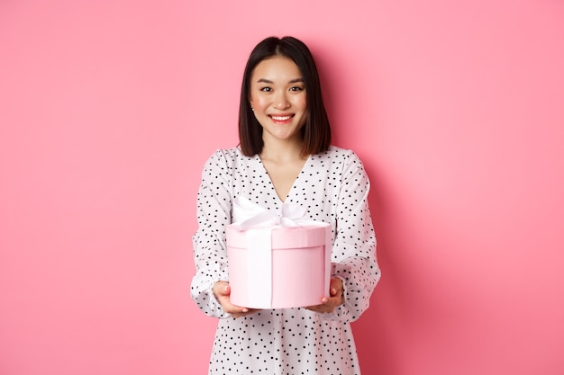 Beautiful asian woman wishing happy holidays giving you gift in cute box standing against pink backg...