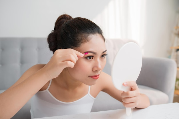 그녀의 눈 옆에 면봉으로 아름 다운 아시아 여자. 개념을 구성합니다.