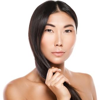 Красивая азиатская женщина со здоровыми черными волосами на белой стене