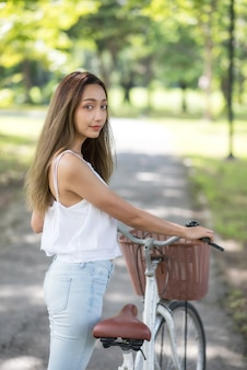Beautiful asian woman with bike in park