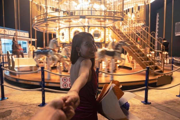 Beautiful asian woman with bouquet holding hands her boyfriend into the glowing carousel in amusement park at night