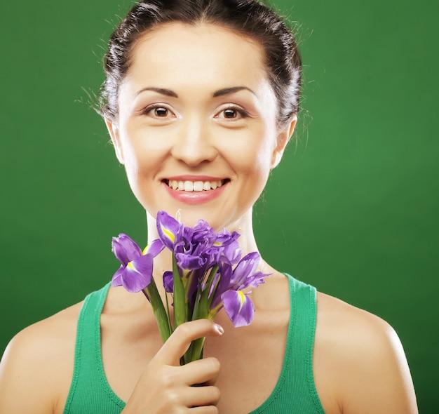 花のアイリスを持つ美しいアジアの女性